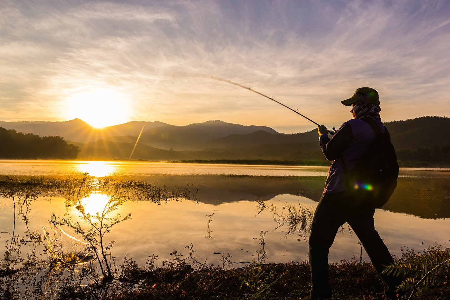 An angler standing by a lake fighting a fish at sunset