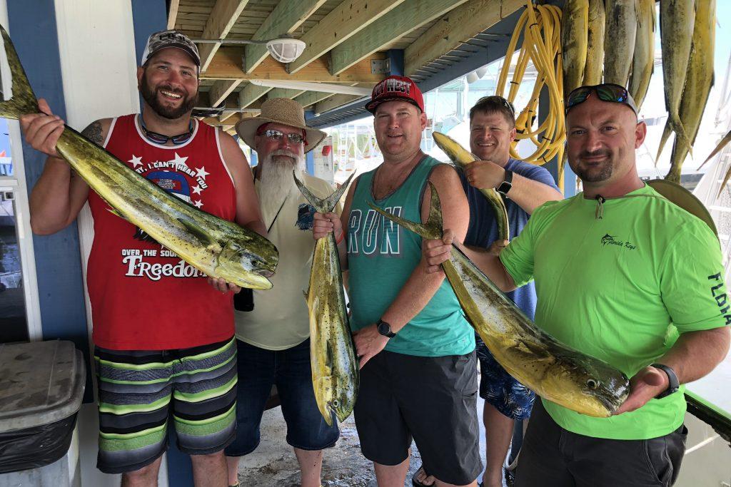 A group of anglers holding Mahi Mahi fish at the dock after a fishing trip