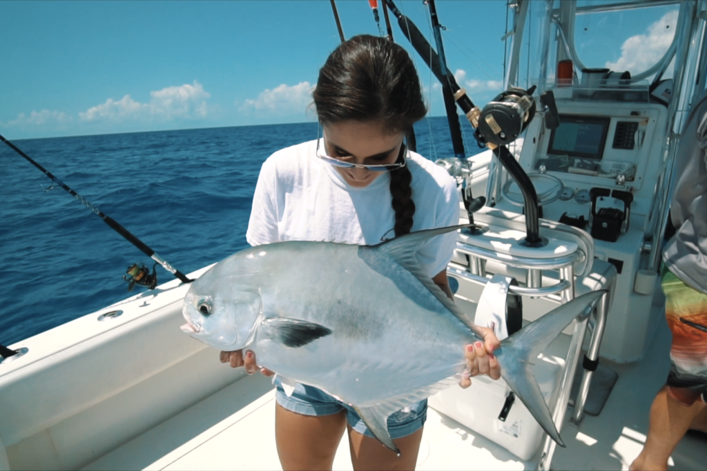 A woman holding a large Permit on a charter fishing boat