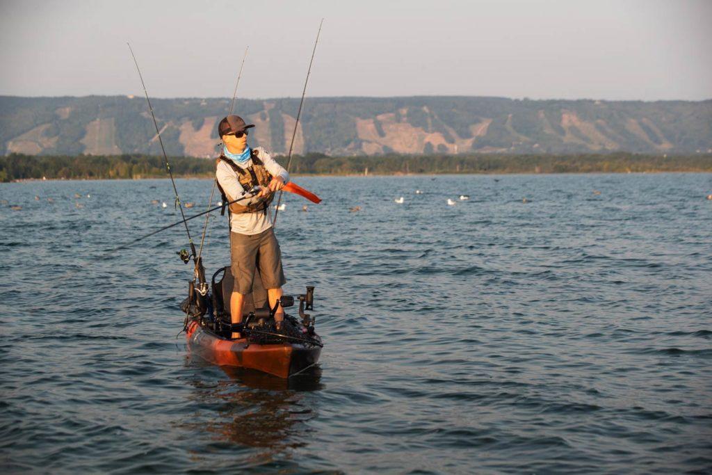 A man kayak fishing at sunrise in Canada