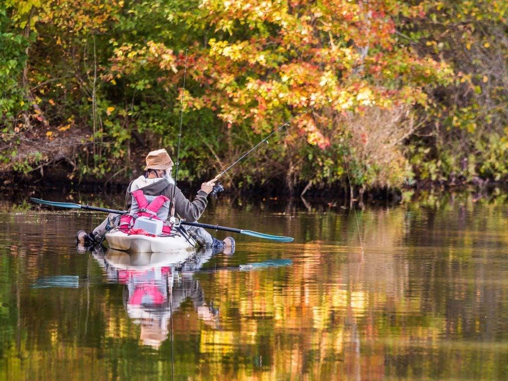 An angler kayak fishing on a river