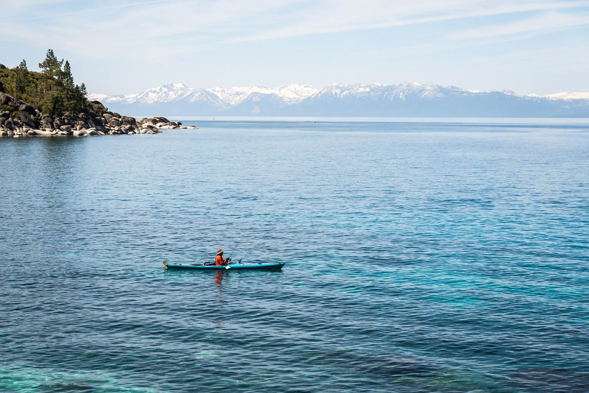 A lone kayak fisherman on Lake Tahoe, with mountains in the background