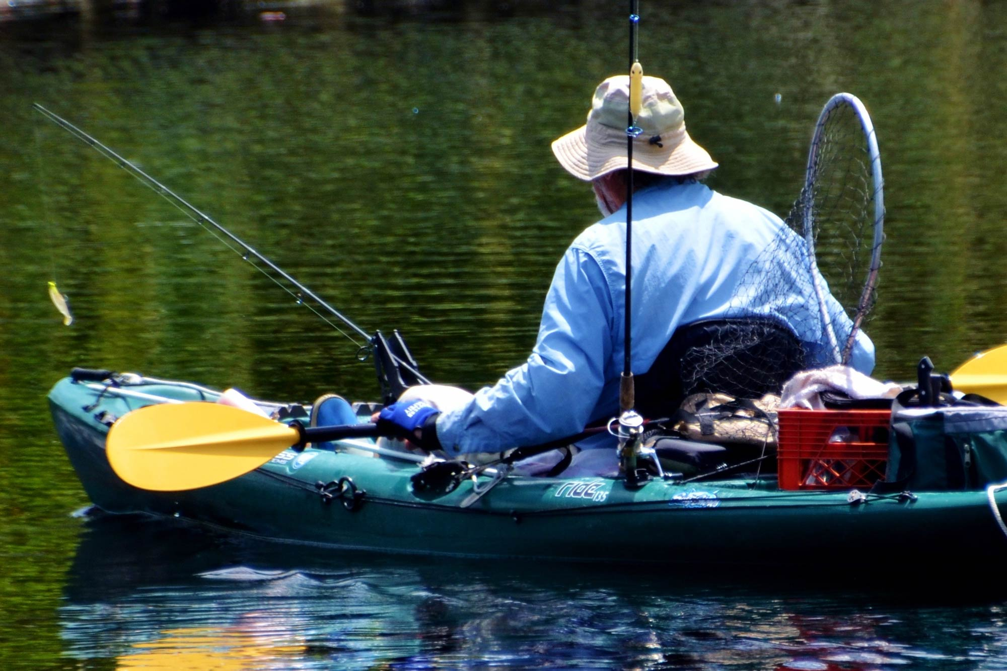 A kayak angler in a cap, with his back to the camera, sitting in his kayak loaded with fishing equipment