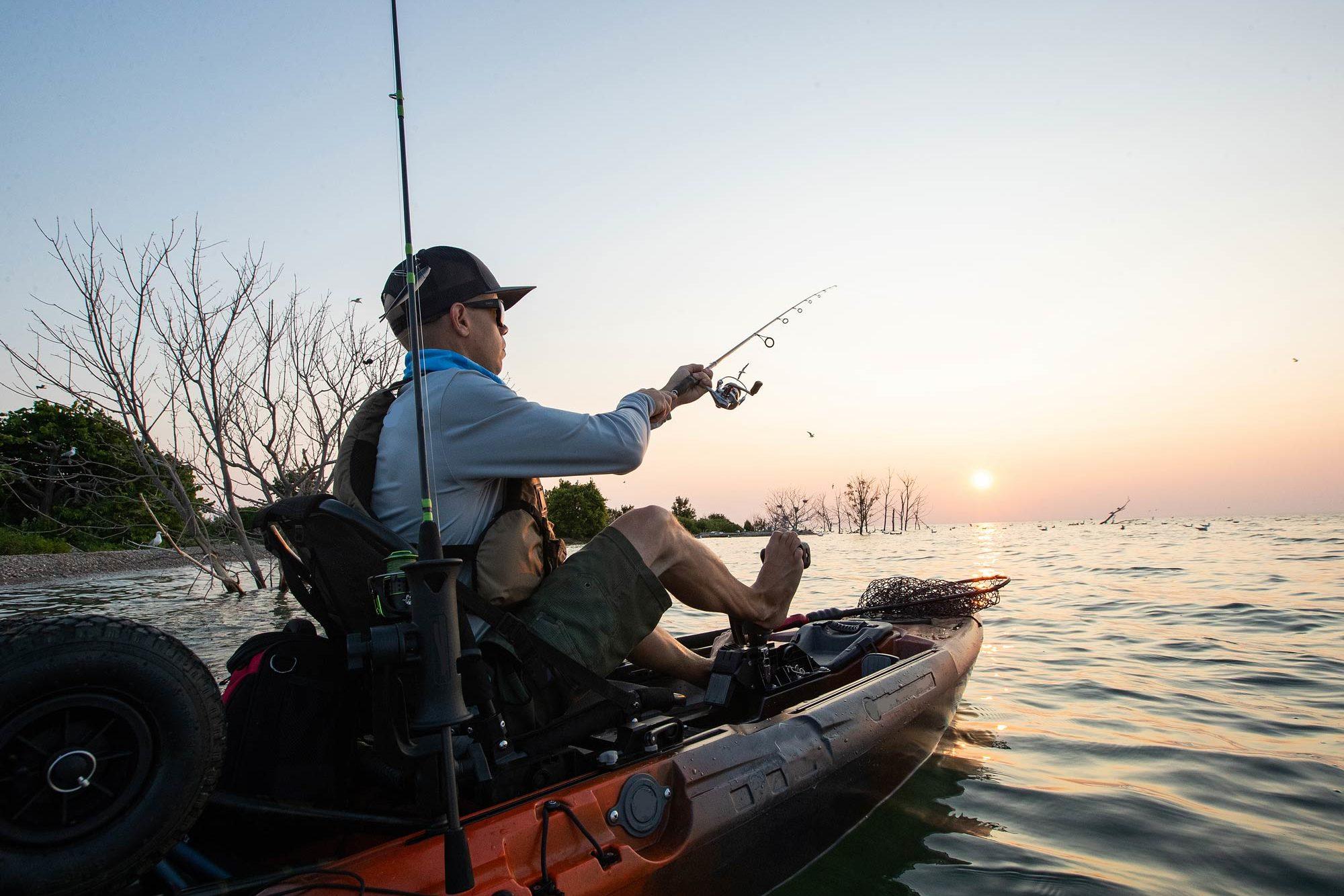 A kayak fisherman fishing from his kayak at sunset