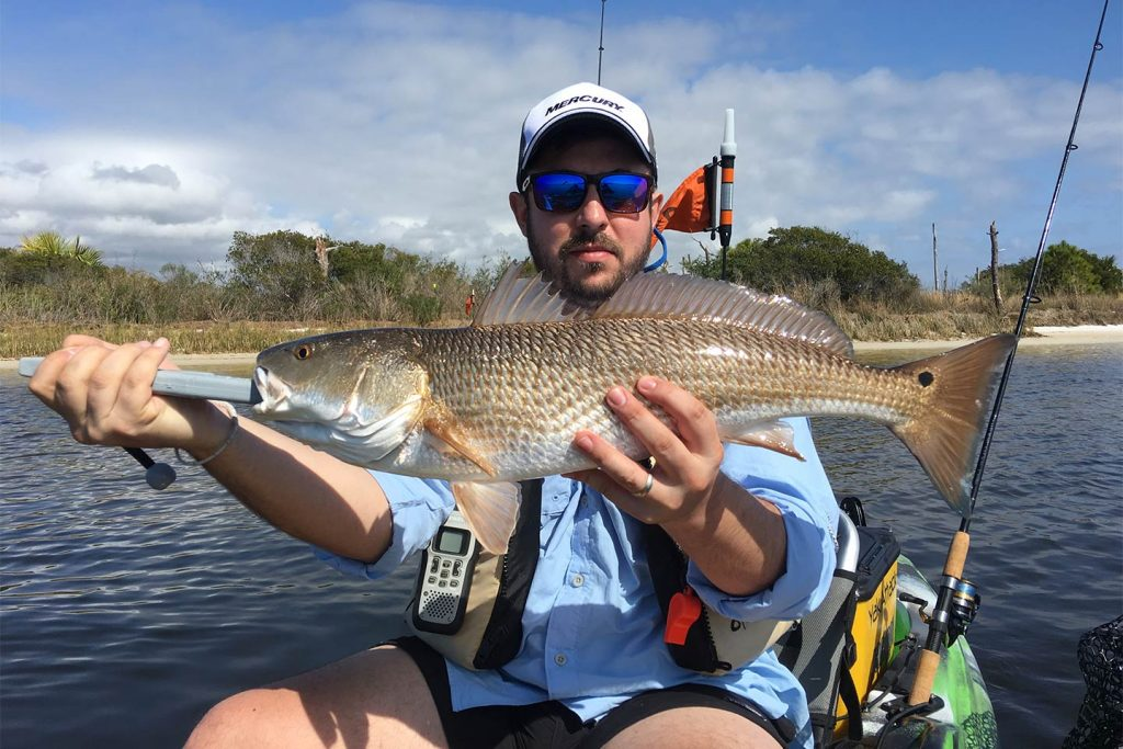 A kayak fisherman holds a Redfish caught fishing inshore from Destin