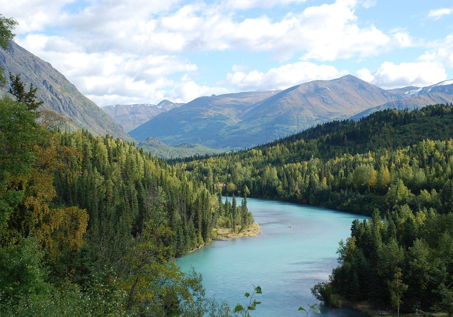 The Kenai River in Alaska, with dense forest on either side and mountains in the distance.