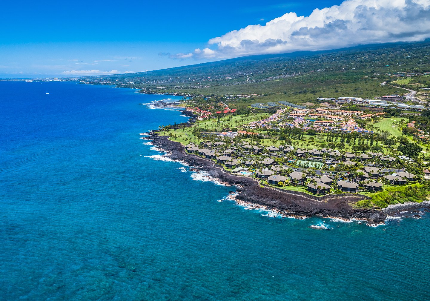 An aerial view of Kailua-Kona, Hawaii, with blue sea to the left and the island to the right