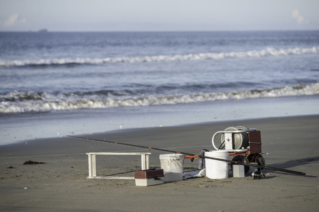 A selection of kontiki and surf fishing equipment on a beach in New Zealand