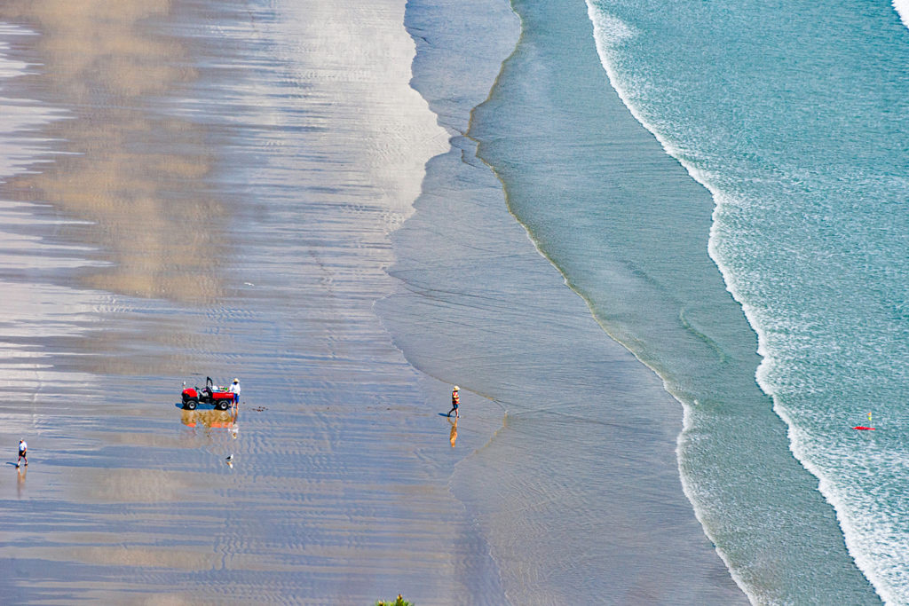 An aerial view of a pair of anglers kontiki fishing using a beach longline system