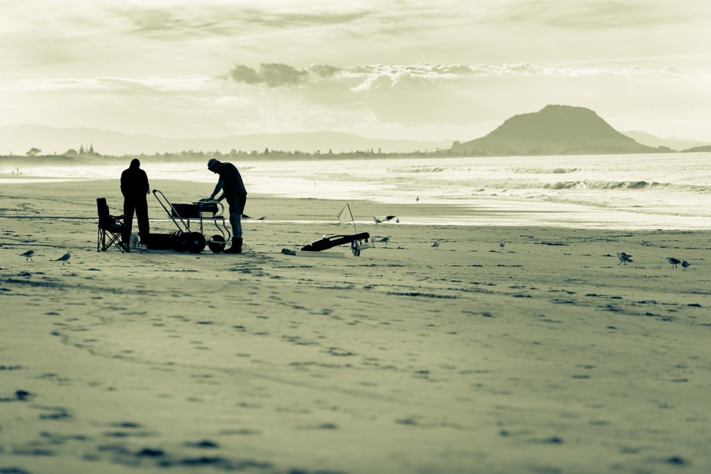 a pair of anglers packing up their kontiki fishing gear on a beach