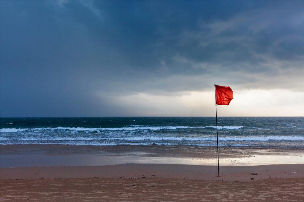 An orange warning flag on a beach