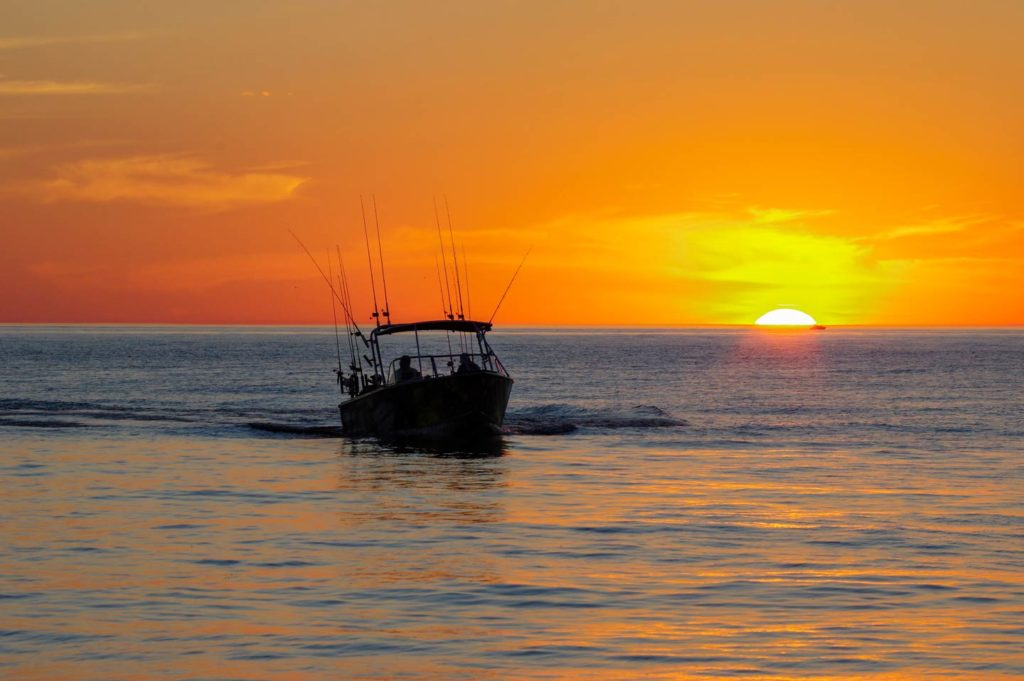 A boat trolls at sunset, with trolling lines visible.