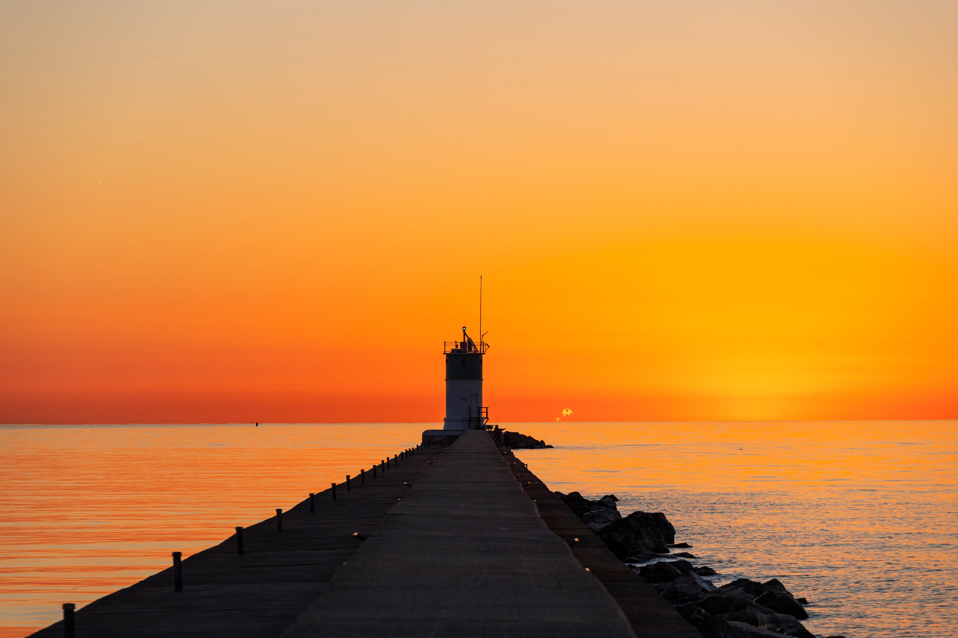 Sunrise over a lighthouse walkway on Lake Michigan in Waukegan, a fishing spot near Chicago