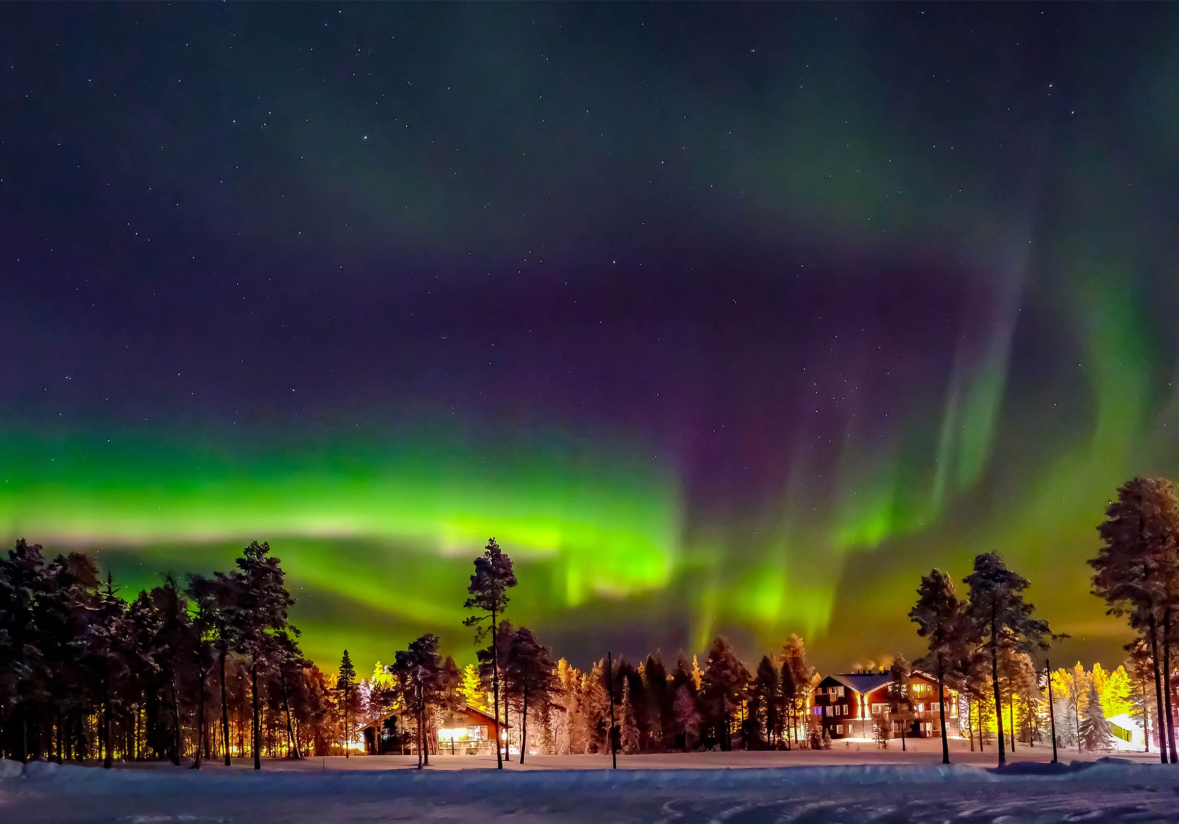 Northern lights with a town in the distance in Lapland, Finland