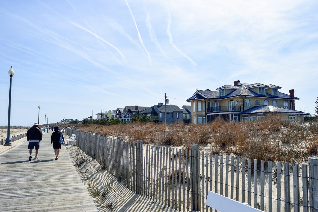 two vacationers on a wooden walkway on a beach in Lewes, Delaware. Houses are visible in the distance on the right.