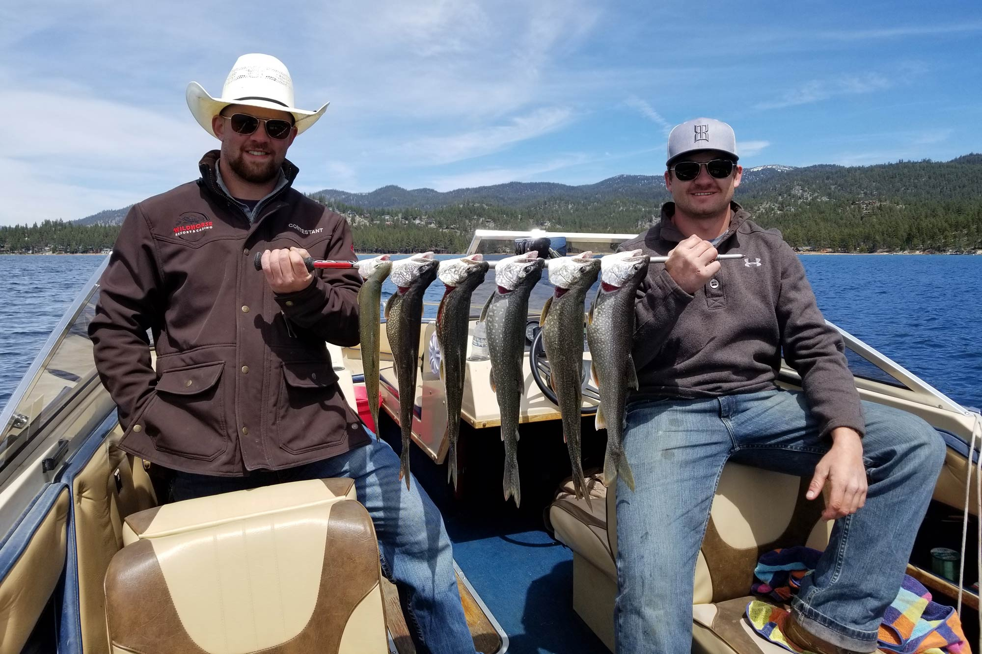 Two fishermen in a boat, holding several Mackinaw Trout with Lake Tahoe in the background