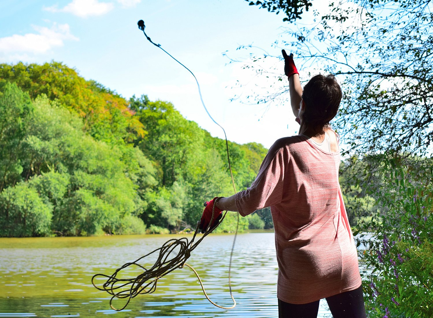 A woman throwing a magnet into a river attached to a rope