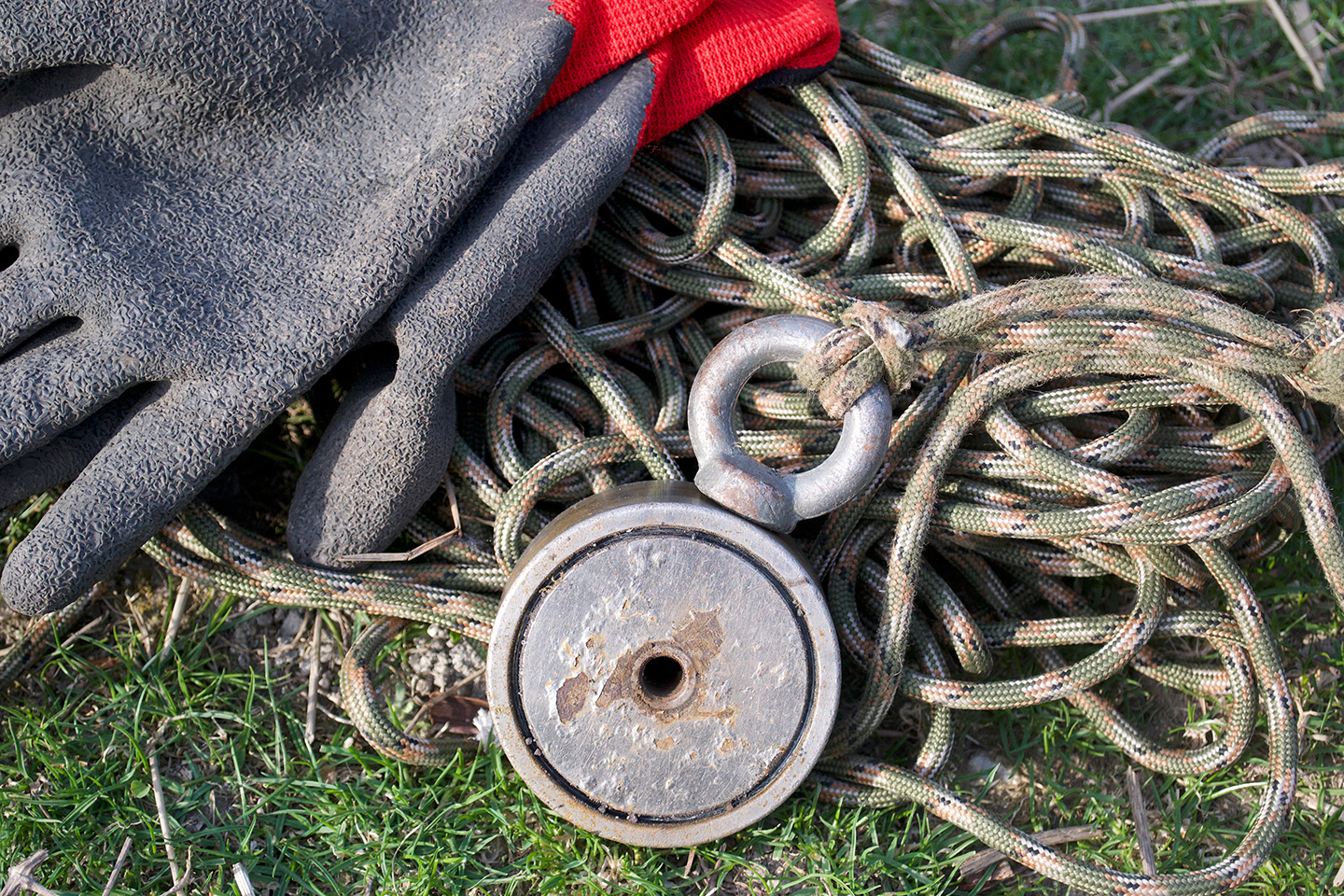 A fishing magnet attached to thick rope, with a set of work gloves