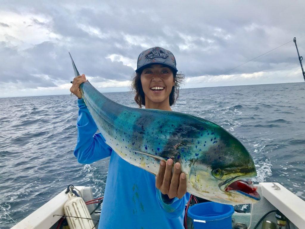 a smiling female angler holding a Mahi Mahi on a fishing boat