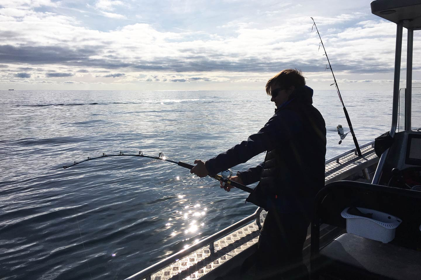 A male angler doing battle with a Sea Trout by jigging in Baltic Sea.