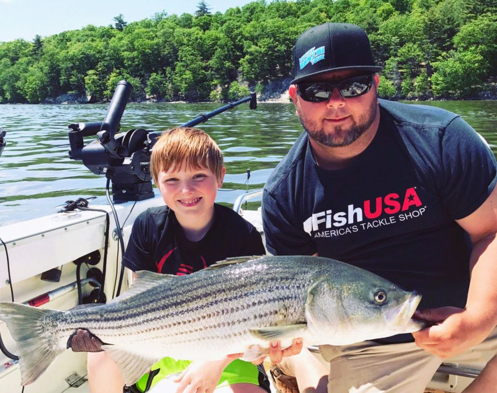 A man and a boy holding a Striped Bass on a fishing boat.
