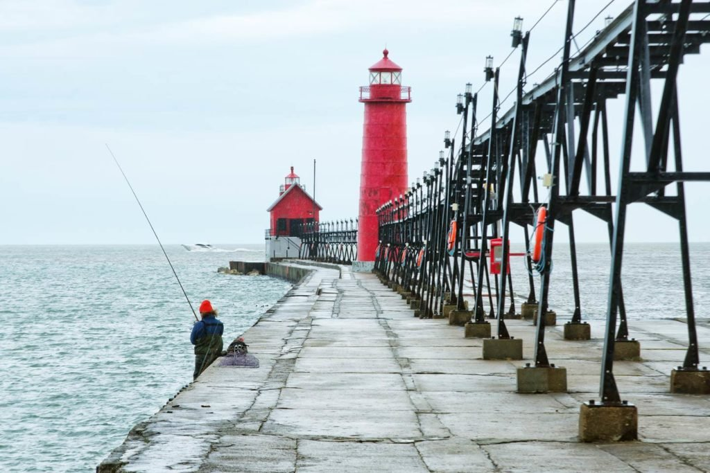 A person fishes from one of the piers leading out to Lake Michigan