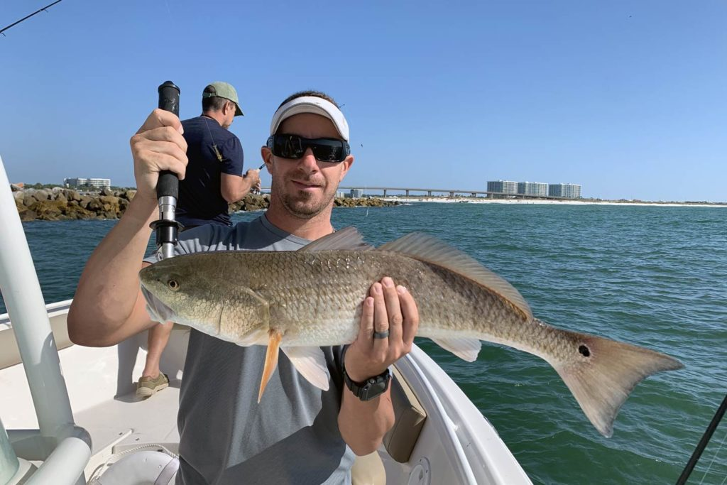 A man wearing sunglasses holds a Redfish up to the camera with the water behind him