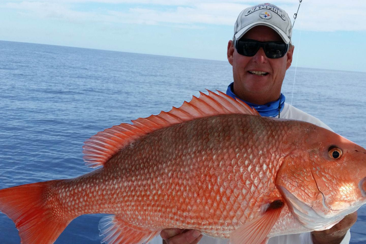 A man holds a large Red Snapper up the camera, with the Gulf of Mexico in the background