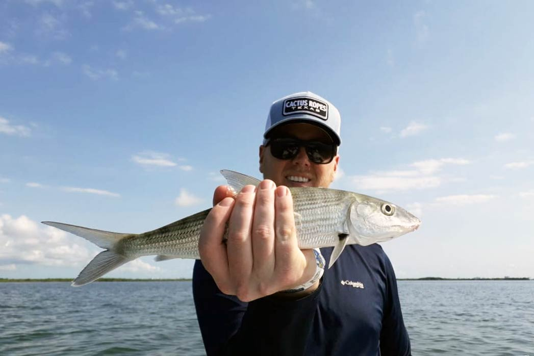A man holds a Bonefish in front of him with the water in the background