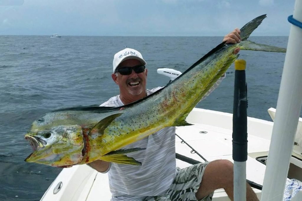 A man holds a large Mahi Mahi up to the camera on a charter boat with the Gulf in the background