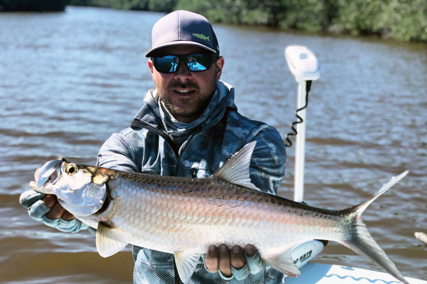 A man holds a large Tarpon up to the camera, with the mangrove waters of Marco Island in the background
