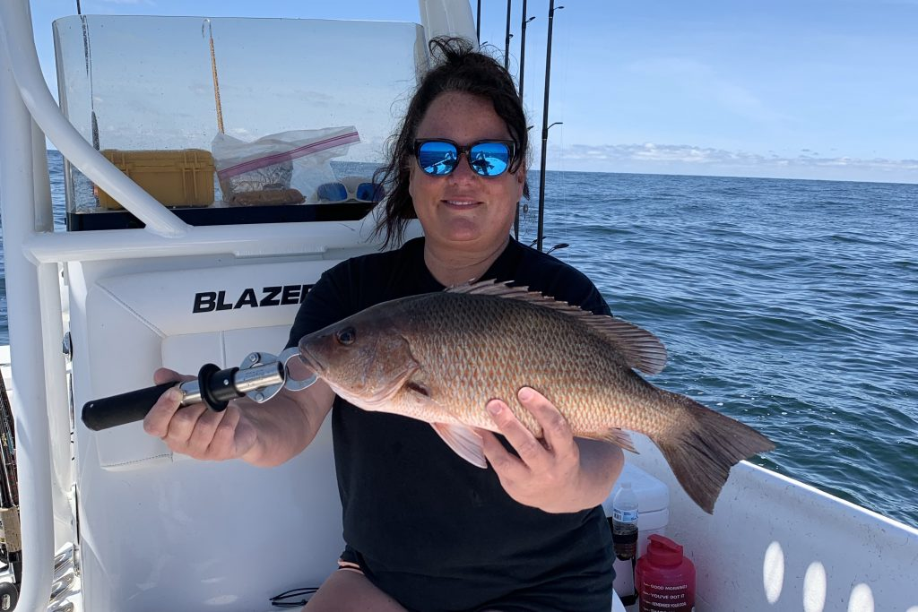 An angler on a charter boat holding a Mangrove Snapper