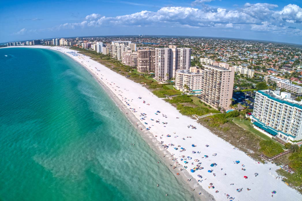 A view of Marco Island's shoreline with a white sandy beach and the ocean to the left, and the city to the right, on a sunny day