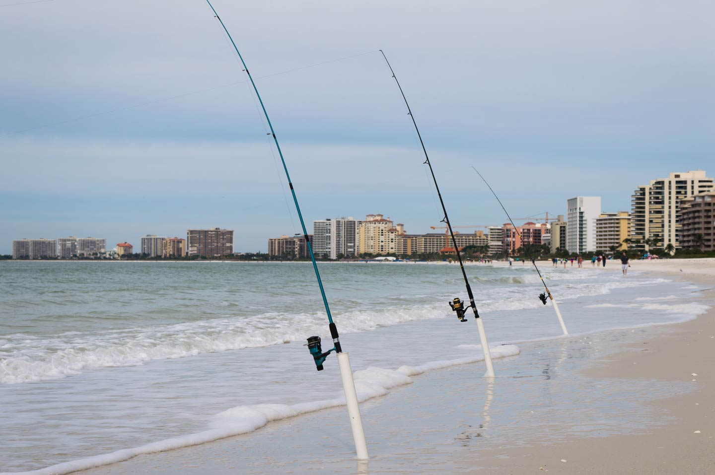 Three fishing rods are lined up along Marco Island's Gulf-facing shoreline, with the sand and the ocean in view