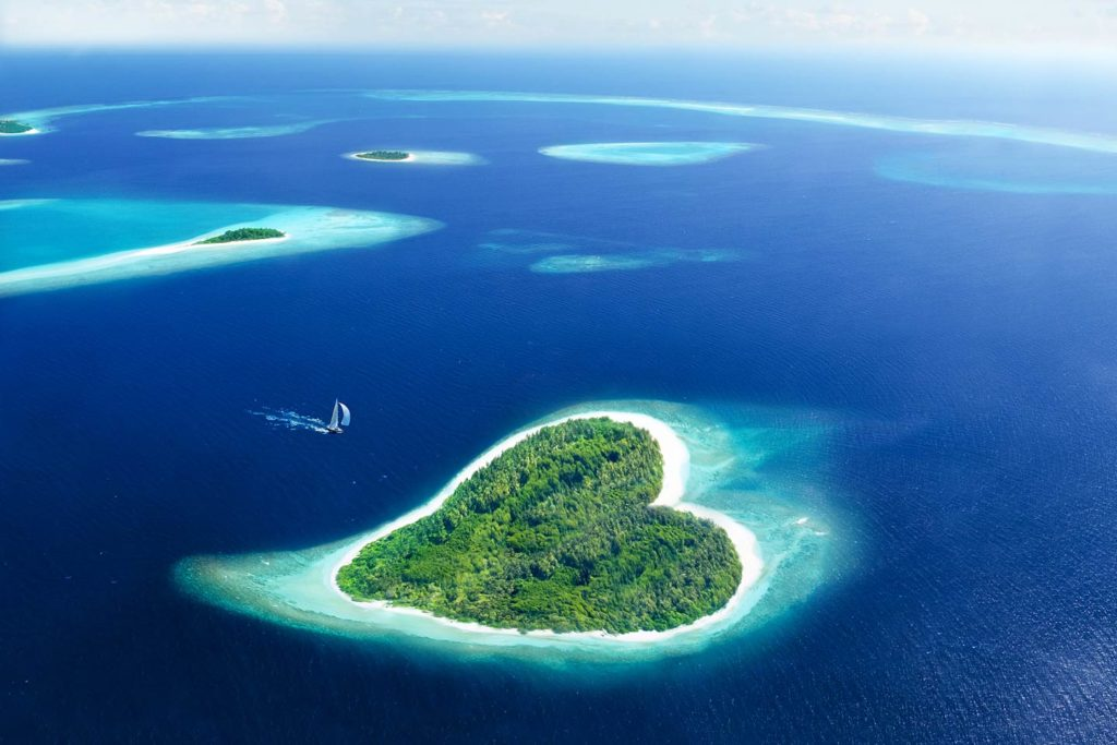 An aerial view of a heart-shaped island in the Maldives.