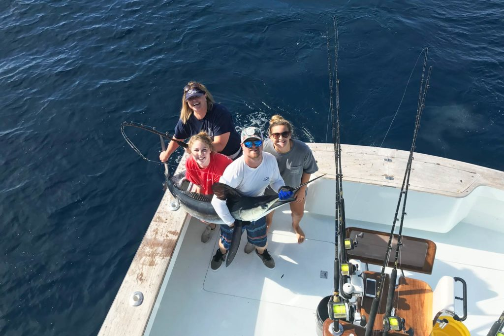 A family of anglers standing in the corner of a boat, holding a White Marlin