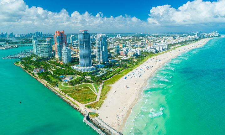 An aerial view of South Beach, Miami, with skyscrapers in the center and green sea to the left and right