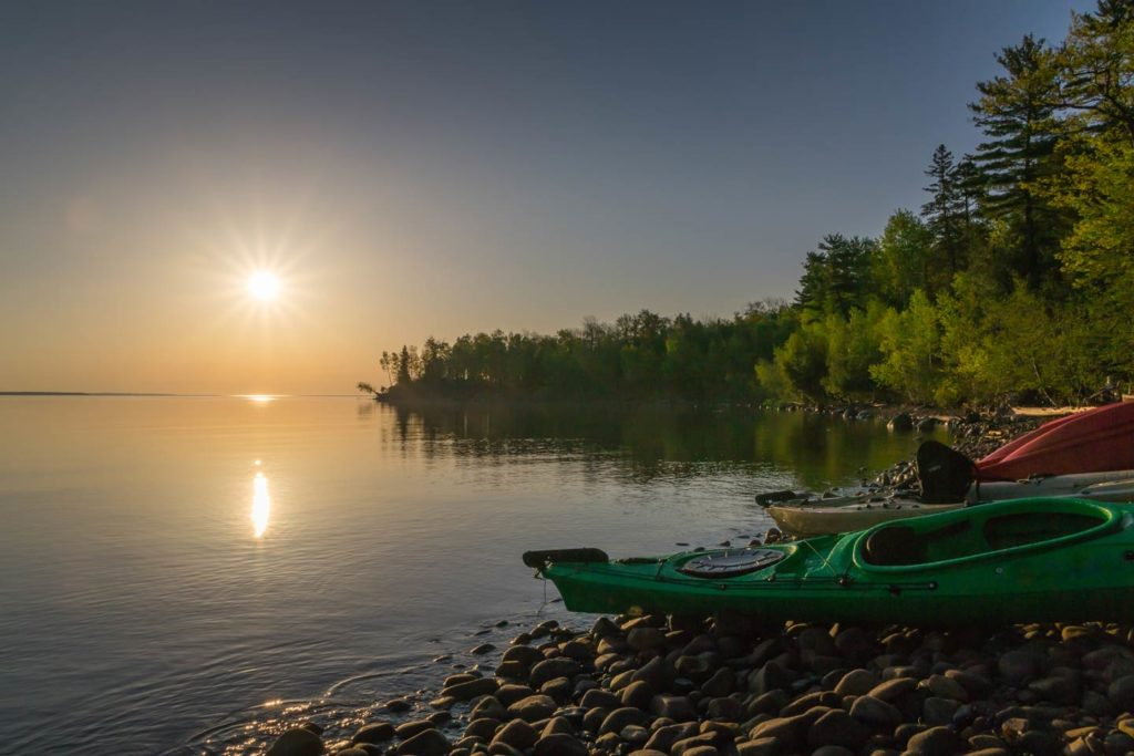 A view of a stone beach with kayaks placed on the ground and the lake in the background at sunset