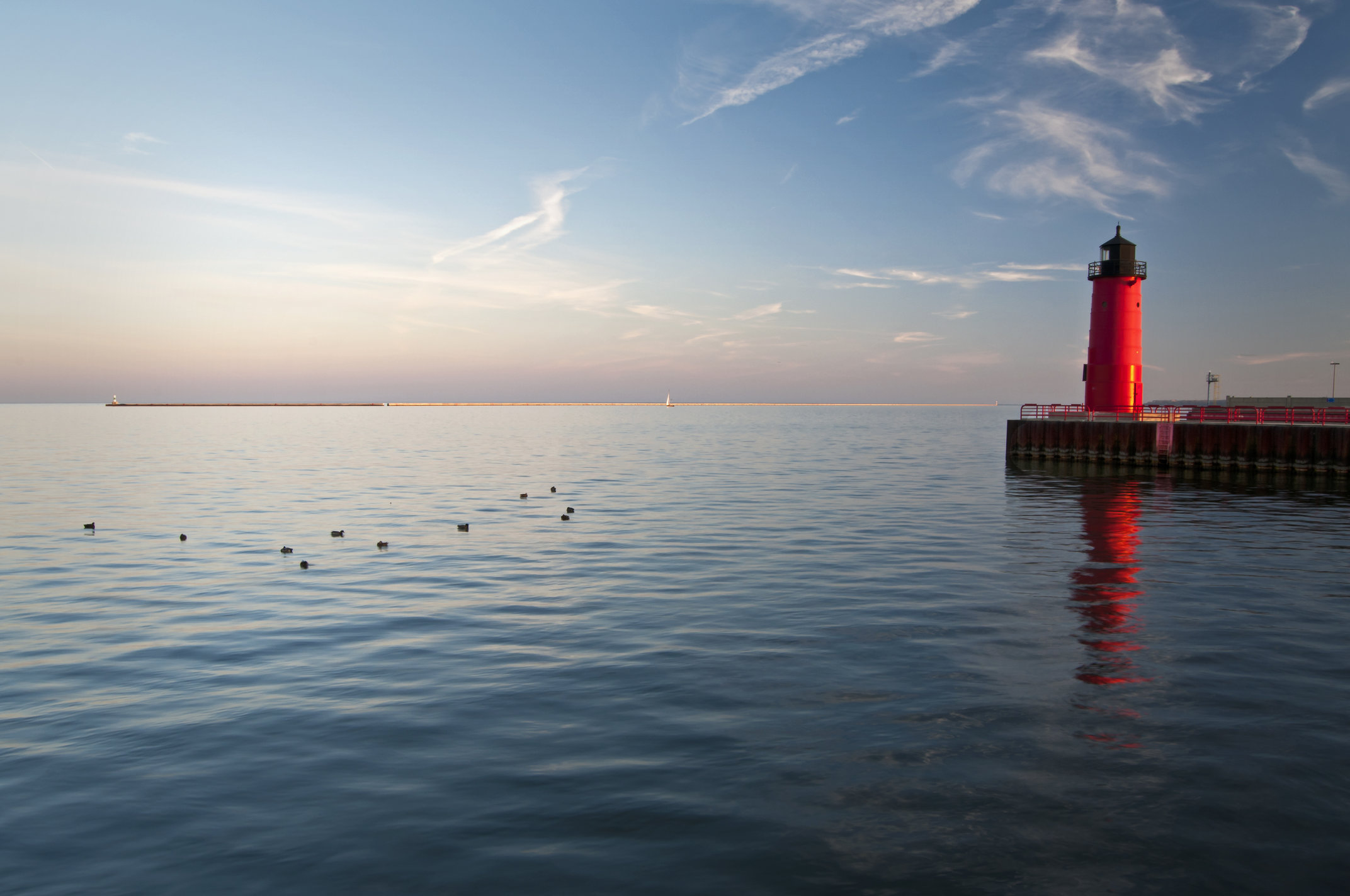 A view over Lake Michigan from the Shore with the lighthouse on the right side