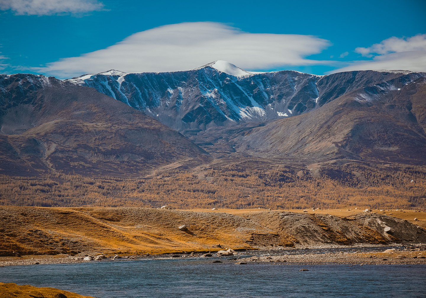 A view of the Mongolian Highlands with water in the foreground and snow-topped mountains in the distance.