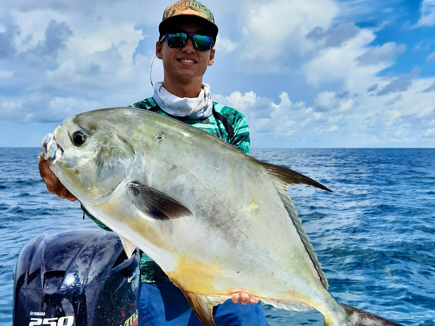 A smiling angler with a cap and sunglasses holding a very big Permit fish