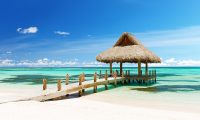 A traditional gazebo on a white sandy beach with turquoise water and blue sky. The typical image of the most popular foreign fishing spots.