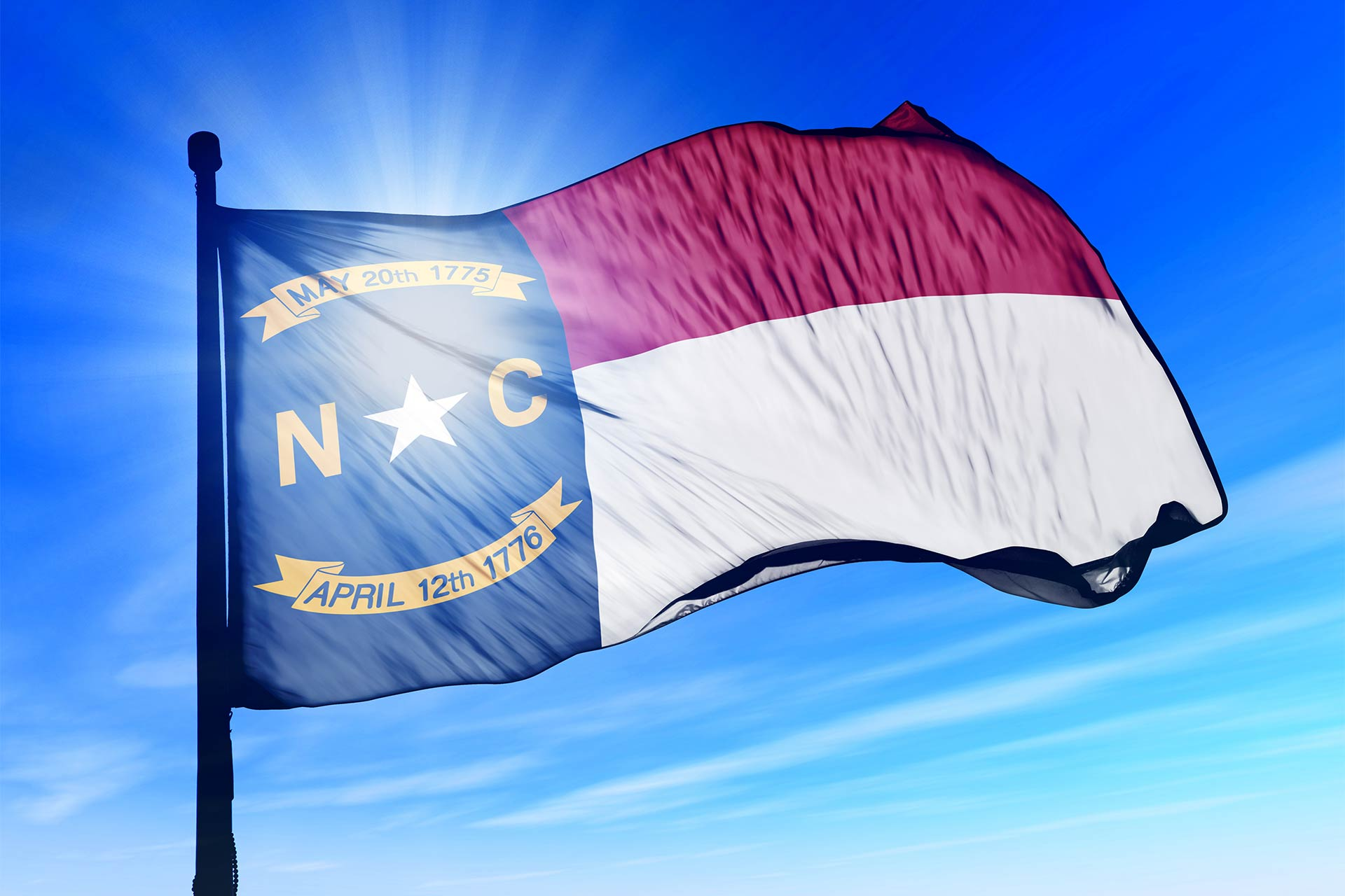 The North Carolina state flag atop a flagpole with the sun shining through from behind
