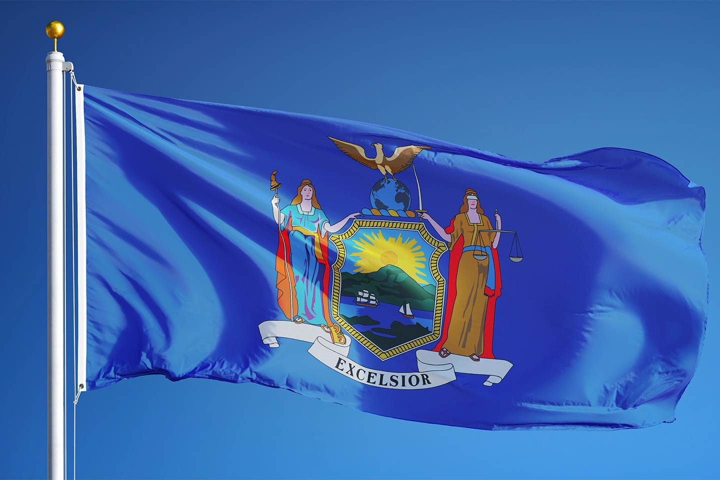 New York state flag flying atop a flagpole against a blue sky