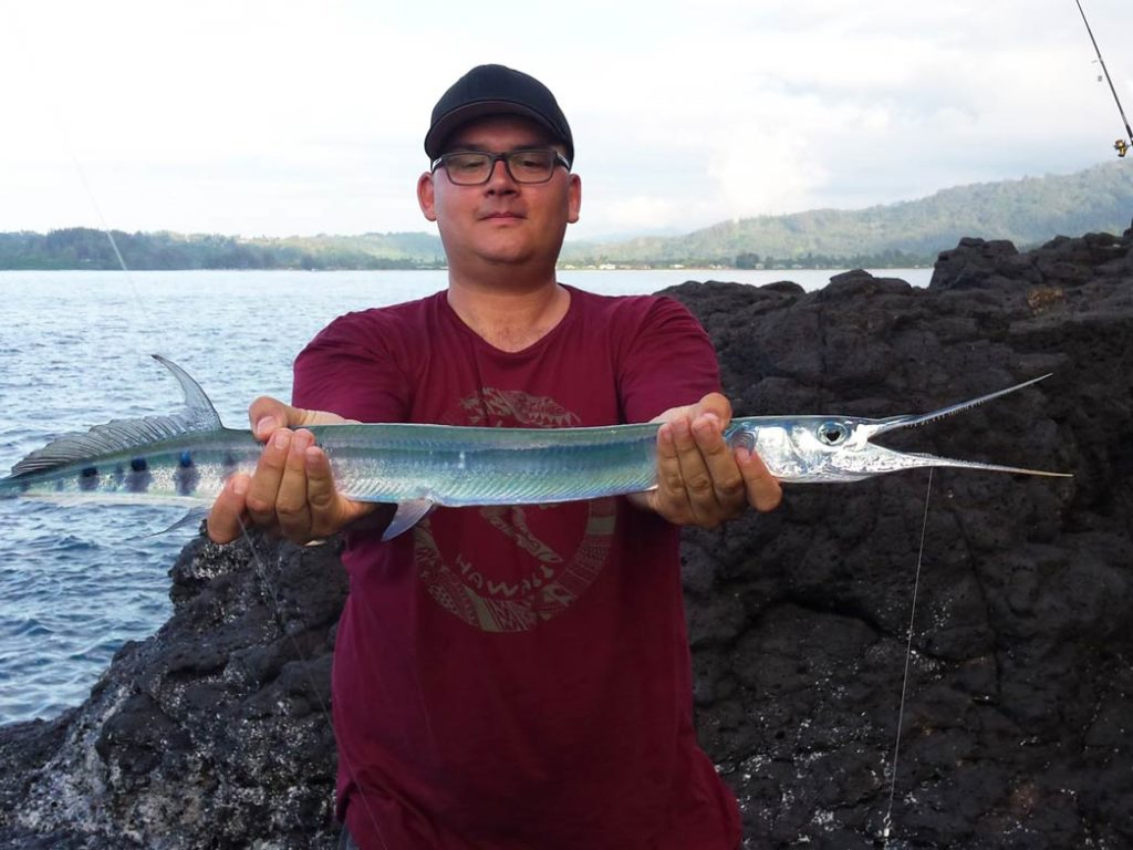 A man holds a Needlefish with rocky structure behind him as well as water