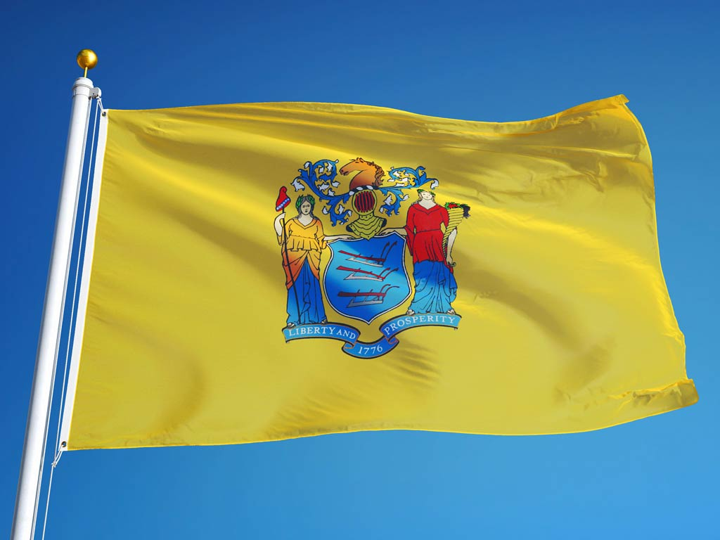 New Jersey state flag waving against clear blue sky