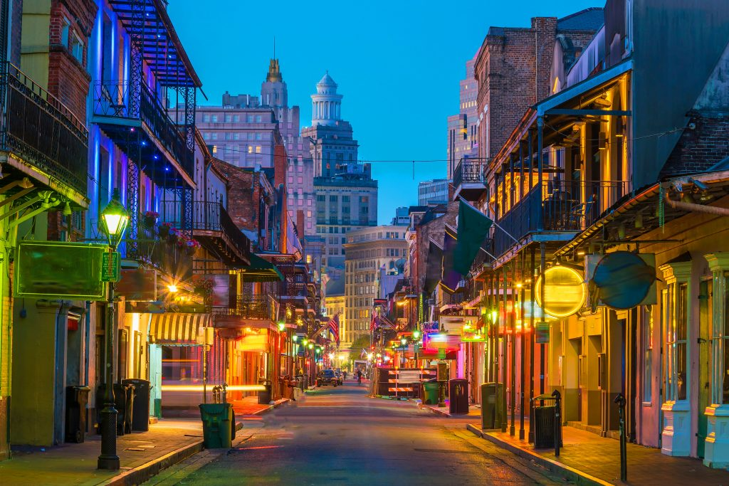 A narrow street in the French Quarter of New Orleans at dusk, with neon signs lighting the street.