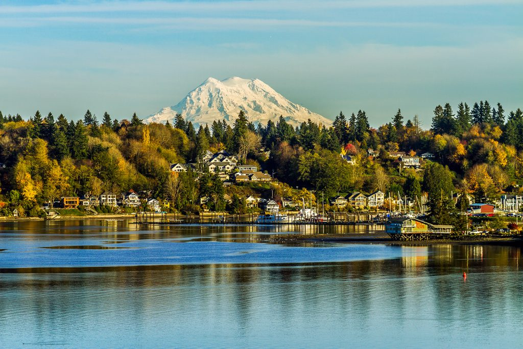 The waterfront in Olympia, Washington, one of the best summer fishing destinations in the US, with buildings by the water and a snowy mountain in the distance
