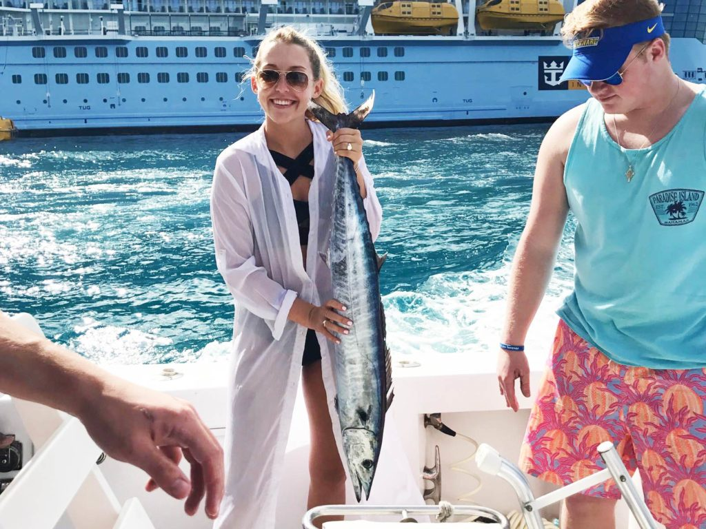 A smiling lady angler in sunglasses holding a big Wahoo fish