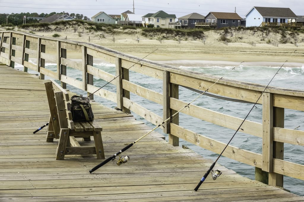 A wooden fishing pier in Outer Banks, with a bench and several rods